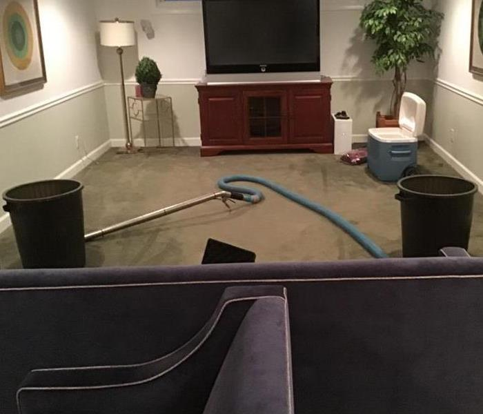 Large Living room with furniture, the ceiling is leaking water all over the room and collecting into two big trash cans