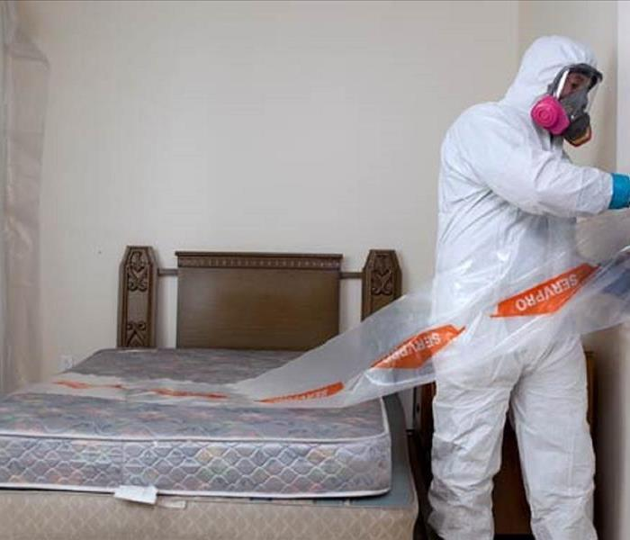 man in white tyvex biohazard suit cleaning a bedroom