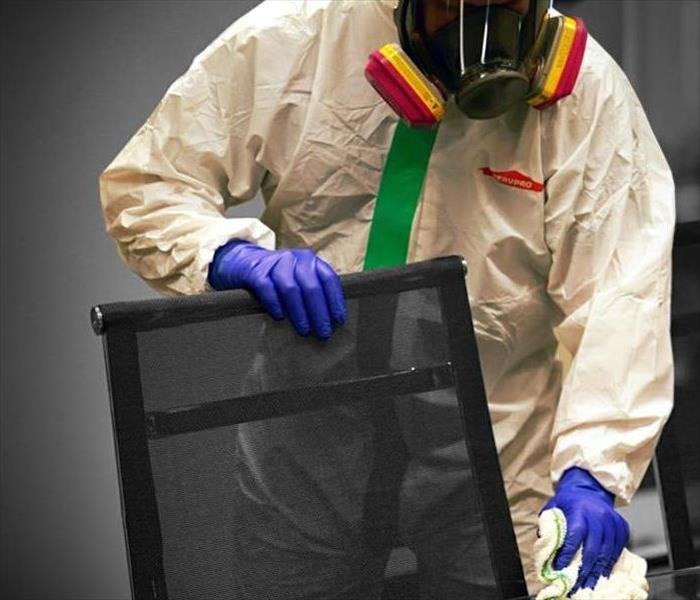 employee in plastic hazmat bio containment suit cleaning office chair